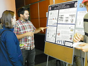 Undergraduate guests interact with graduate students at a poster session