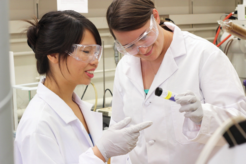 Two graduate students working with the Center for Sustainable Nanotechnology examine a vial in a chemistry laboratory