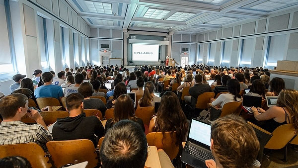 Dozens of students in a lecture hall look toward a PowerPoint presentation