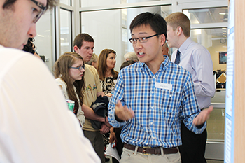 A chemistry major explains his undergraduate research at a poster session