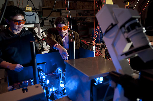 Professor David Schwartz and a graduate student work with blue lasers in a dark research lab