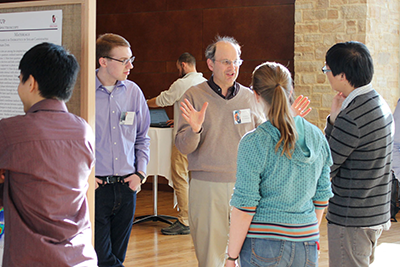 Physical chemistry faculty member talks to students at a poster session