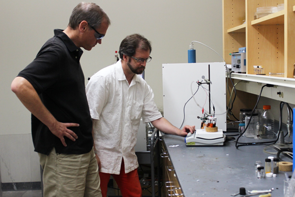 Researchers look at a model fuel cell system in the lab