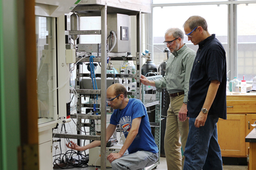 Graduate student David Mannel, along with Stahl and Root, work on a continuous-flow oxygen reactor.