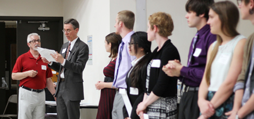Several undergraduate student award recipients stand in a line to be recognized by the department chair at the 2015 Student Awards Ceremony