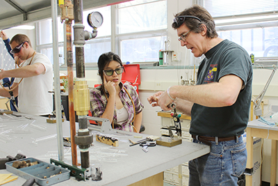 Master Glassblower Tracy Drier (right) trains graduate students in a scientific glassblowing class