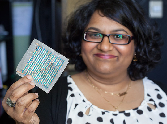 Professor Trisha Andrew holds a solar cell printed on paper
