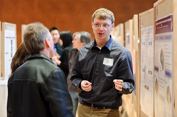 An undergraduate researcher uses his hands to talk with visitors about his research poster at Union South's Varsity Hall