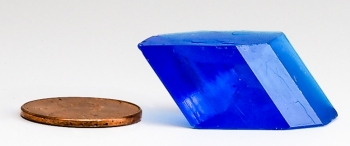 A blue crystal sits next to a penny for size reference