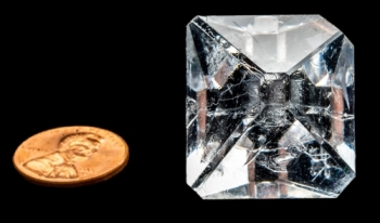 A clear crystal sits next to a penny for size comparison