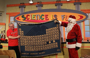 Professor Bassam Shakhashiri displays a periodic table during his annual holiday chemistry demonstration