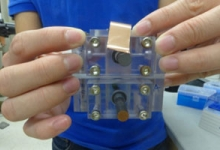 A student displays a solar-charged battery